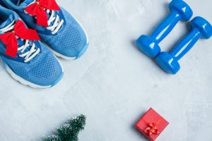 Christmas sport composition with shoes, dumbbells and red gift b